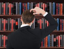 Young man in a suit scratching his head Stock Images