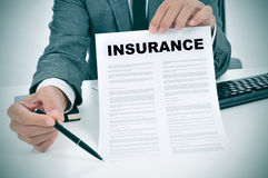 Young man in suit showing an insurance policy Stock Images
