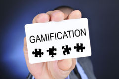 Young man in suit shows a signboard with the word gamification. Young caucasian man in suit shows a signboard with the word gamification written in it Stock Image