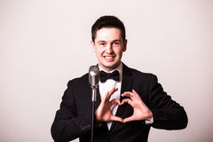 Young man in suit singing with the microphone and make love sign with hands. Royalty Free Stock Images