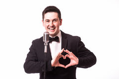 Young man in suit singing with the microphone and make love sign with hands. Stock Images