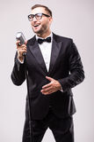 Young man in suit singing over the microphone with energy. Isolated on white background. Singer concept Stock Image
