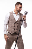 Young man in suit singing over the microphone with energy. Isolated on white background. Singer concept Stock Photos