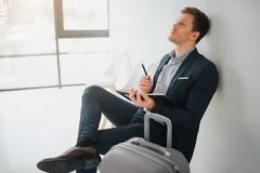 Young man in suit sit in room and look up. He hold notebook and pen. Guy think. Grey suitcase stand beside him. Young man in suit sit in room and look up. He stock photography