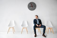 Young man in suit sit on white chair in white room. He lean to wall. Guy wait fo flight in waiting room. He sits alone. Young man in suit sit on white chair in royalty free stock photos