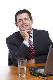 Young man in suit sitting happy at desk Stock Photo