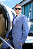 Young man in suit standing in the door of executive jet Royalty Free Stock Photo
