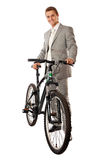 Young man in a suit standing next to a bike. Attractive young man in a suit standing next to a bike and smiling, isolated over white Royalty Free Stock Photography