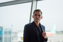 A young man in a suit stands at the airport at the aircrafts background. A young man in a suit stands at the airport near the window at the airplanes background stock photography