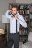 Young man in a suit takes his tie off Stock Photos