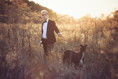 Young man in suit and tie with a greyhound dog in aut Stock Photography