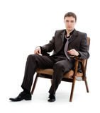 A young man in a suit and tie, sitting in a chair. A young man in a suit and tie, sitting in a chair, isolated on white background Royalty Free Stock Images
