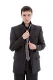 A young man in a suit, tie a tie. Stock Image