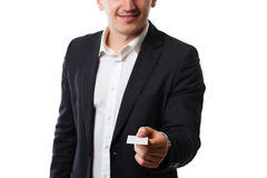Young man in a suit on a white background gives credit card. Attractive young man in a suit on a white background gives credit card stock photography