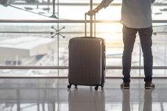 Young man with suitcase luggage in airport terminal Royalty Free Stock Images