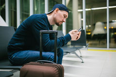 A young man with a suitcase sits in the airport waiting room and uses a mobile phone. Night flight, transfer, waiting at Stock Photos