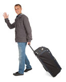 Young man with suitcase waving hello, full length Stock Photos