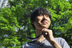 Young man in summer. Handsome chinese young man in park,outdoors Royalty Free Stock Image