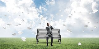 Young man in summer park on bench do not want to see anything stock photography