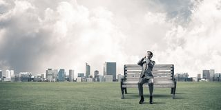 Young man in summer park do not want to see anything. Young shocked businessman sitting on wooden bench and covering eyes with palms royalty free stock photo