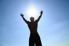 Young man and the sun. Silhouette of a young boy on a background of blue sky and sun Stock Images