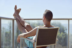 Young man sun tanning in a chair Stock Photo