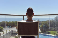 Young man sun tanning in a chair Stock Images