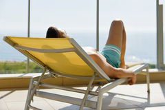 Young man sun tanning in a sunlounger. Closeup of a young caucasian man in swimsuit lying down face up on a sunlounger in a terrace Stock Photos