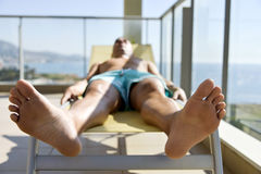 Young man sun tanning in a sunlounger. Closeup of a young caucasian man in swimsuit lying down face up on a sunlounger in a terrace Stock Photography