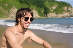 Young man sunbathes on beach Royalty Free Stock Image