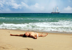 Young man sunbathing at a beach Stock Photos