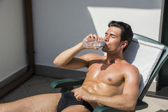 Young Man Sunbathing and Drinking from Water Bottle Royalty Free Stock Photography