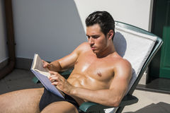 Young Man Sunbathing on Lounge Chair Reading Book Stock Image