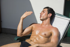 Young Man Sunbathing on Lounge Chair Stock Image