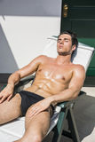 Young Man Sunbathing on Lounge Chair Royalty Free Stock Photo