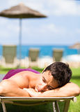 Young man sunbathing and relaxing on a deckchair. On vacation: young man sunbathing and relaxing on a deckchair near the beach Royalty Free Stock Image