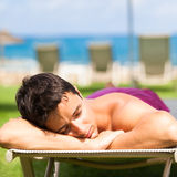 young man sunbathing and relaxing on a deckchair Stock Image