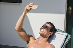 Young Man Sunbathing and Taking Selfie picture Royalty Free Stock Photo