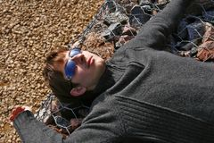 Young man in sunglasses. One teenager is lying on a metal fence in sunny day. He dressed in sweater and sunglasses on his head. Blurry pebble in the background Royalty Free Stock Images