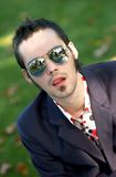 Young Man With Sunglasses. Outdoor portrait of a fashionable young man, looking up, wearing a sports jacket and reflective sunglasses Stock Photos