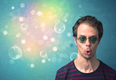 Young man with sunglasses and bokeh colourful lights Royalty Free Stock Image