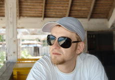 Young man in sunglasses and cap sitting Stock Photos