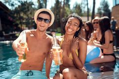 Young man is sunglasses and cheerful woman cheering with beer bottles in swimming pool. Young men is sunglasses and cheerful women cheering with beer bottles in Stock Images