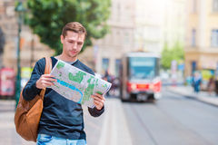 Young man in sunglasses with a city map and backpack in Europe. Caucasian tourist looking at the map of European city in Royalty Free Stock Image