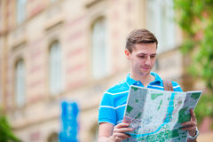 Young man in sunglasses with a city map and backpack in Europe. Caucasian tourist looking at the map of European city in. Happy young man with a city map and a Royalty Free Stock Image