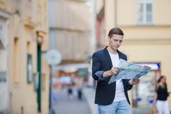 Young man in sunglasses with a city map and backpack in Europe. Caucasian tourist looking at the map of European city in Stock Image
