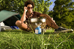 Young man, in sunglasses, cooking food on gas camping stove, smiling, front view, portrait (surface level) Stock Photography