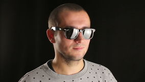 Young man in sunglasses dancing music isolated black background stock footage