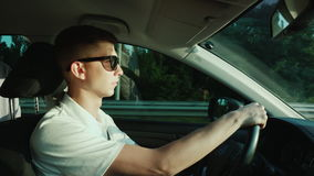 A young man in sunglasses is driving a car stock footage