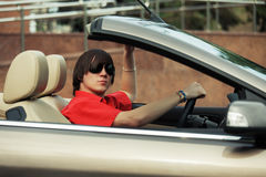 Young man in sunglasses driving convertible car Stock Photos